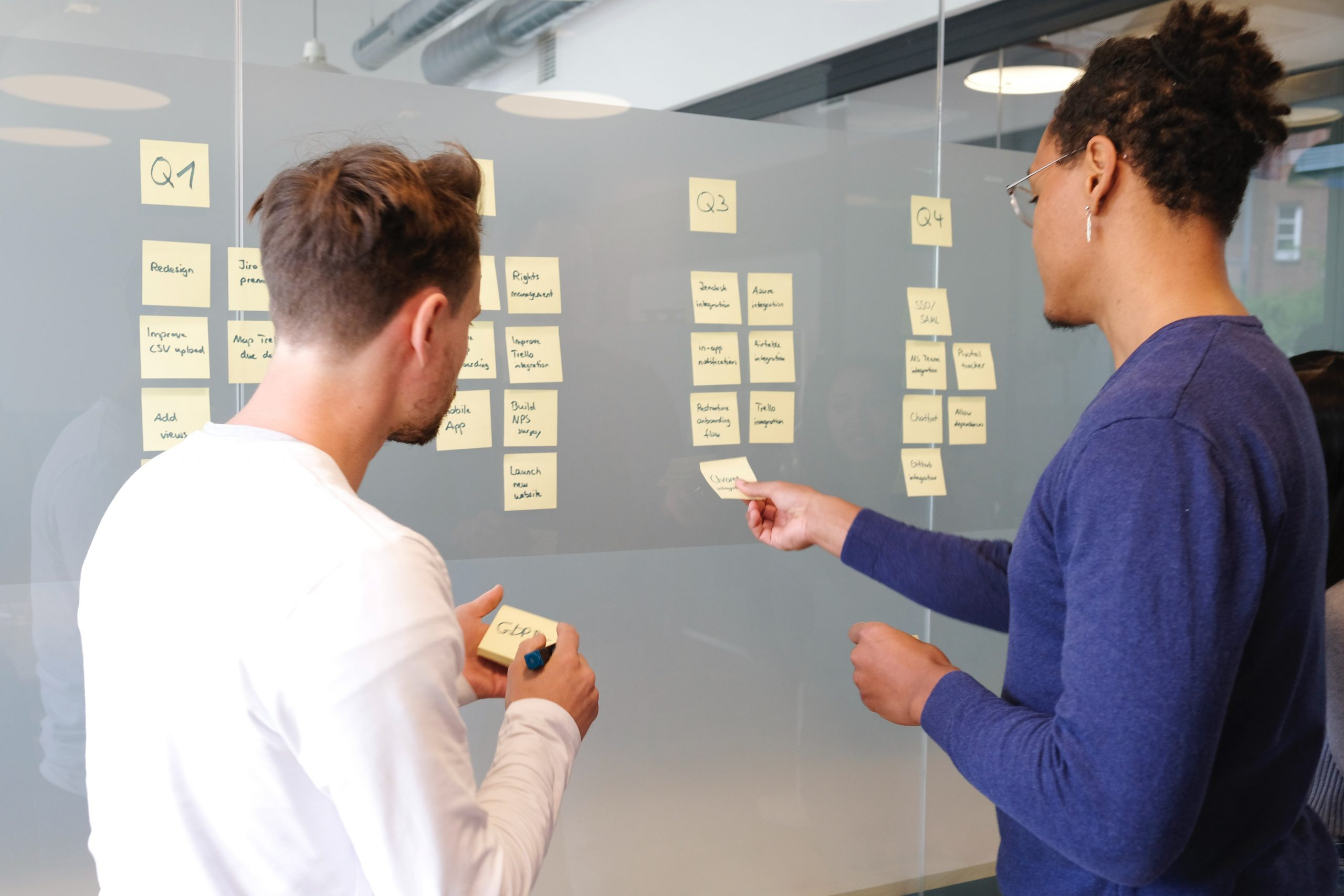 man and woman organising research information in kanban style using post it notes on a grey board