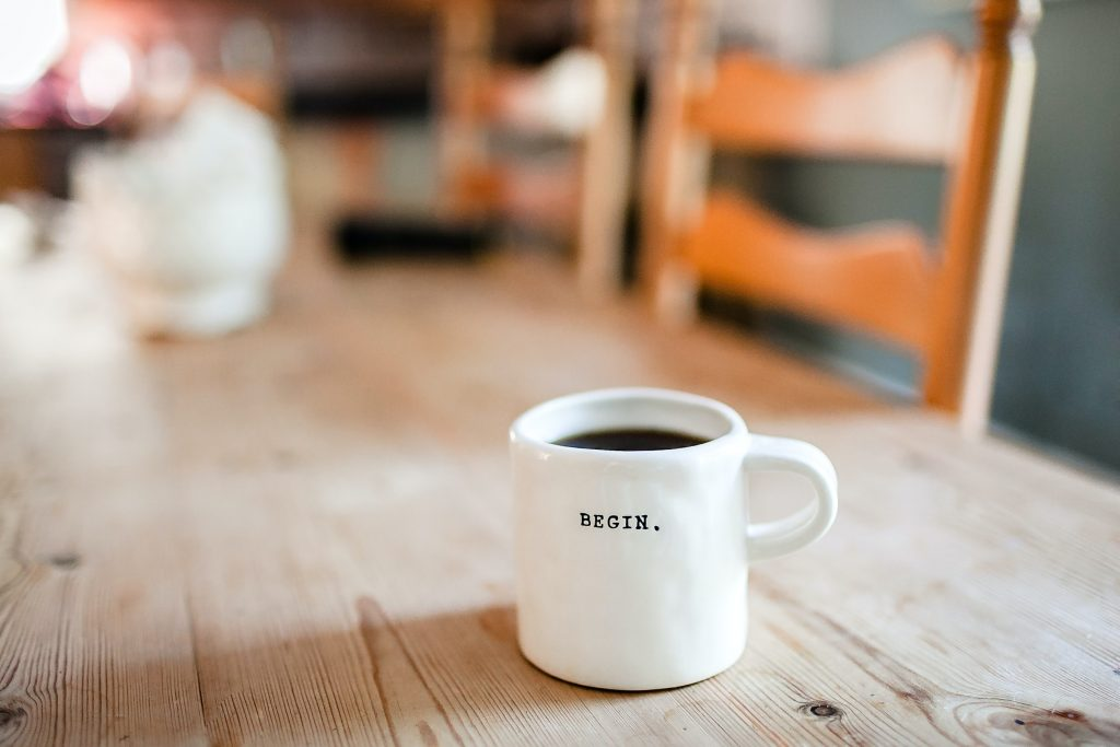 white mug that says begin on a wooden table with a chair in the background